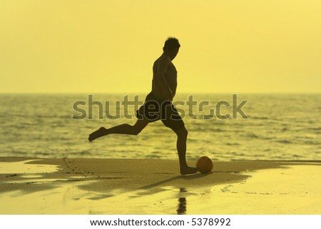 man shooting the ball in the beach - stock photo