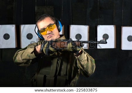 Man shooting with rifle at a target in shooting range - stock photo