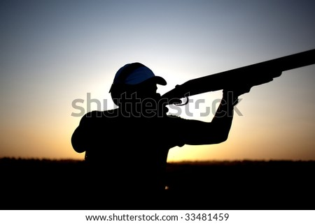 Man shoots with his gun silhouette - stock photo