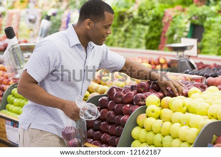 Man shopping in produce section of supermarket - stock photo