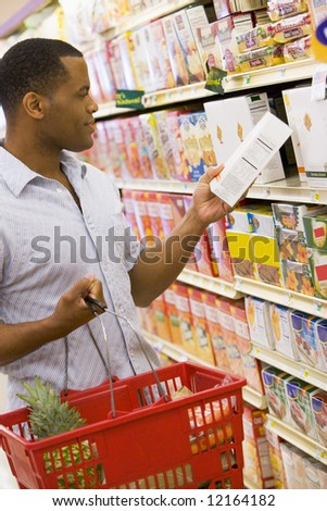 Man shopping in supermarket checking contents of box - stock photo