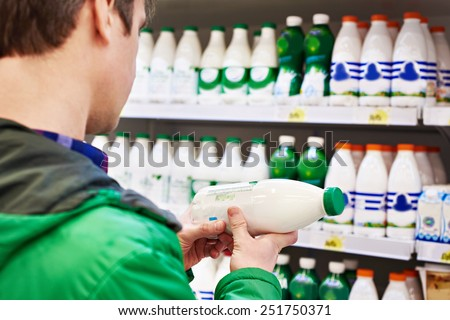 Man shopping milk in grocery store - stock photo