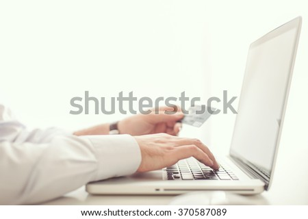 Man shopping online with his credit card from his laptop computer - stock photo