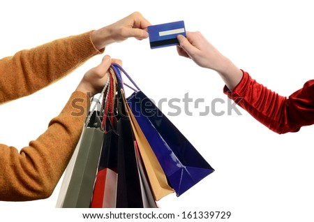 Man shopping, woman paying. Man hand holding many shopping bags, woman giving him a credit card. Isolated on white. - stock photo