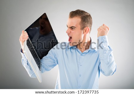 Man shouting at his laptop in fear - stock photo