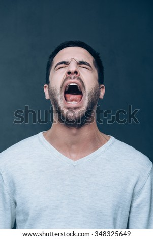 Man shouting. Furious young man keeping eyes closed and mouth open while standing against grey background - stock photo