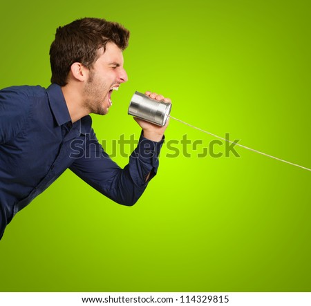 Man Shouting In Tin Can On Green Background - stock photo