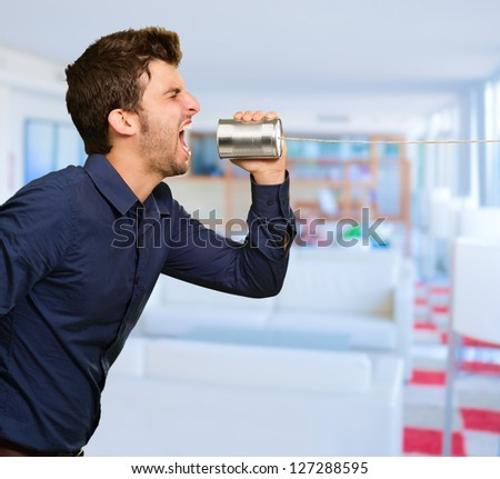 Man Shouting In Tin Can Telephone, Indoors - stock photo