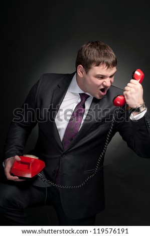 Man shouting into a red telephone. - stock photo
