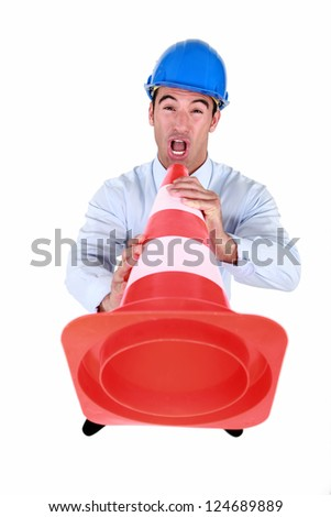 Man shouting into traffic cone - stock photo
