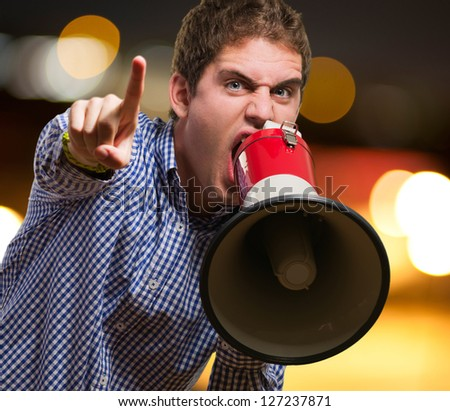 Man Shouting On Megaphone And Pointing Up With His Finger against a city by night - stock photo