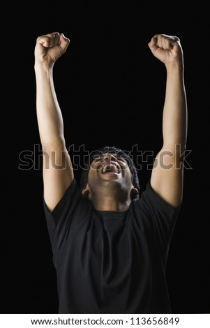 Man shouting with his arms raised - stock photo
