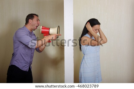 Man shouts at woman through a megaphone, she covers her ears with the hands. Conflict concept