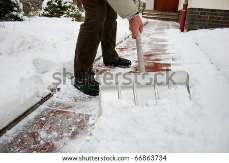 Man shoveling snow at a footpath - stock photo