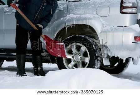 Man shoveling snow from his car - stock photo