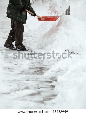 Man shoveling snow from the sidewalk in front of his house after a heavy snowfall in a city - stock photo