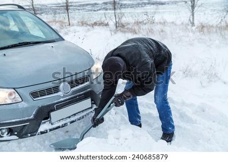 Man shoveling snow to free his stuck car - stock photo