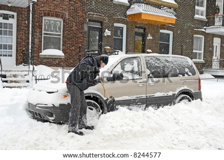 Man shovelling and removing snow from his car during a snow storm. - stock photo