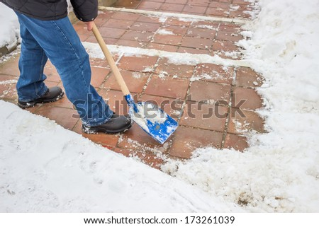 Man shovelling snow from the sidewalk after fresh snowfall
