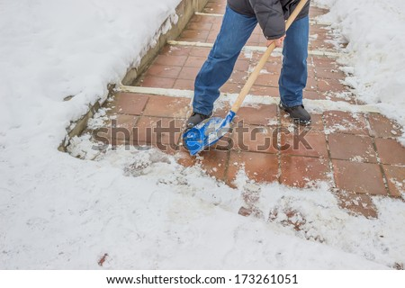 Man shovelling snow from the sidewalk after fresh snowfall  - stock photo