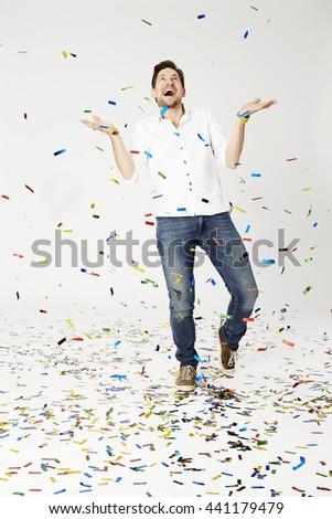 Man showered with confetti, studio shot - stock photo