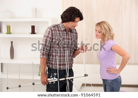 Man showing a woman how to set up an antenna - stock photo