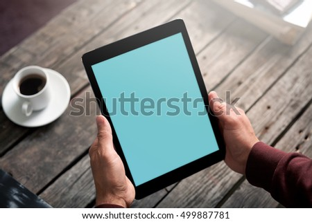 Man showing digital tablet at a cafe. Clipping path included.
