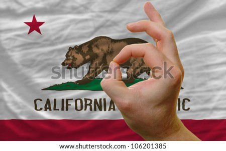 man showing excellence or ok gesture in front of complete wavy american state flag of california symbolizing best quality, positivity and success - stock photo