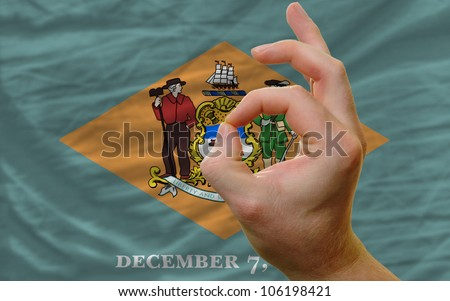 man showing excellence or ok gesture in front of complete wavy american state flag of delaware symbolizing best quality, positivity and success - stock photo