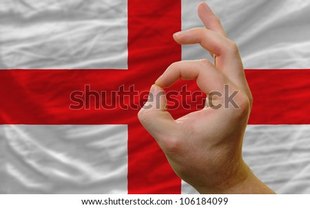 man showing excellence or ok gesture in front of complete wavy england national flag of  symbolizing best quality, positivity and success