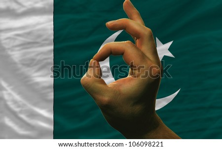 man showing excellence or ok gesture in front of complete wavy pakistan national flag of  symbolizing best quality, positivity and success - stock photo