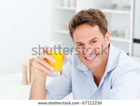 Man showing glass of orange juice to the camera sitting in the kitchen