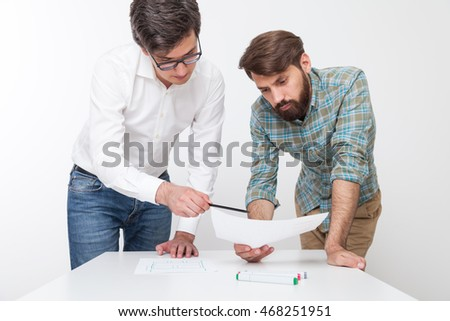 Man showing his colleague mistake in blueprints. Concept of team work for benefit of company