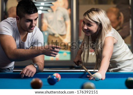 Man Showing His Girlfriend Where To Hit The Ball - Young Caucasian Woman Receiving Advice On Shooting Pool Ball While Playing Billiards - stock photo