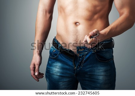 Man showing his muscular body. Stripper unzips jeans and belt