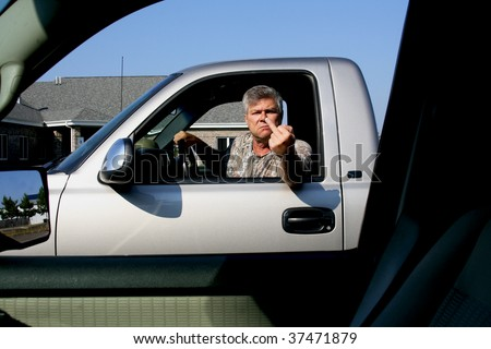 man showing middle finger in anger to another driver - stock photo