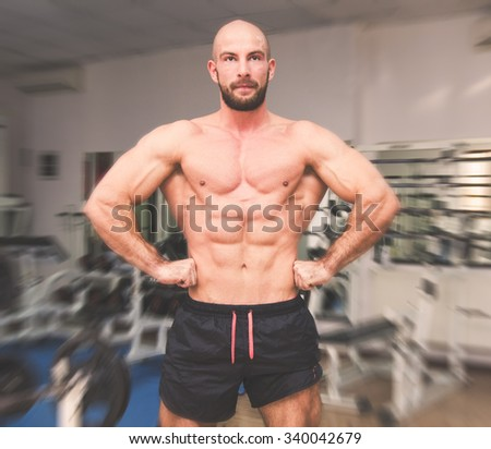 Man showing off his muscles at the gym with soft vintage filters applied suggesting a great chest, abs and biceps workout - stock photo
