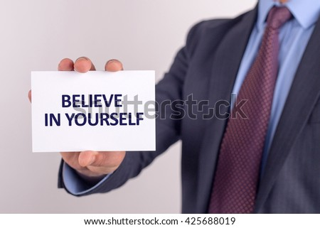Man showing paper with BELIEVE IN YOURSELF text