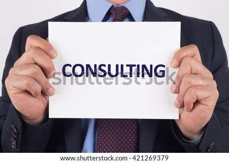 Man showing paper with CONSULTING text - stock photo
