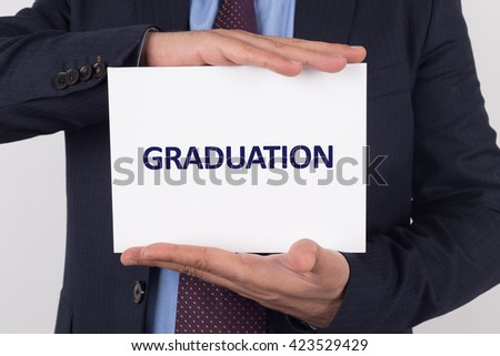 Man showing paper with GRADUATION text - stock photo