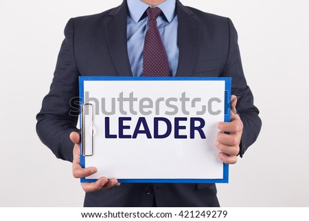 Man showing paper with LEADER text - stock photo