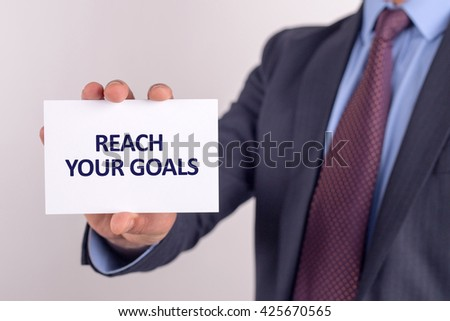 Man showing paper with REACH YOUR GOALS text