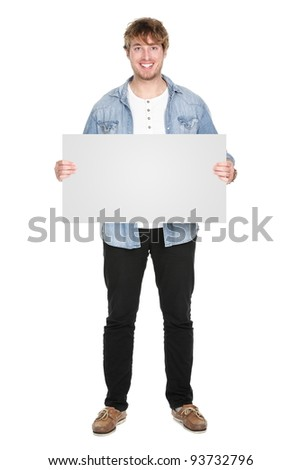 Man showing sign standing in full body. Casual young guy holding blank empty banner sign isolated on white background. Caucasian male model in his twenties. - stock photo