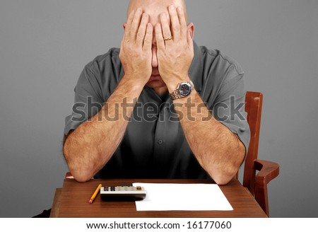 Man showing signs of stress while working budget - stock photo