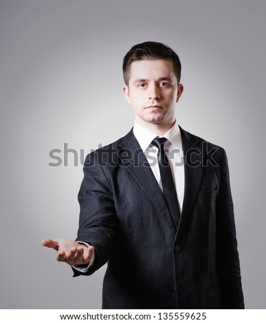 man showing something on the palm of his hand on a gray background - stock photo