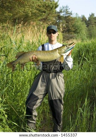 Man showing the catch a big pike - stock photo