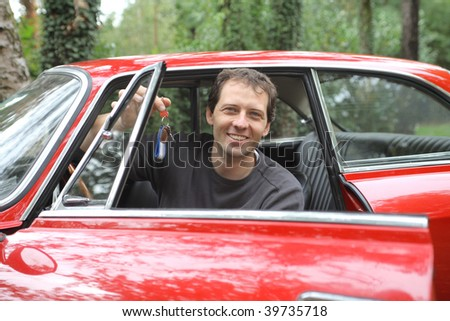 man showing the keys of  vintage car - stock photo