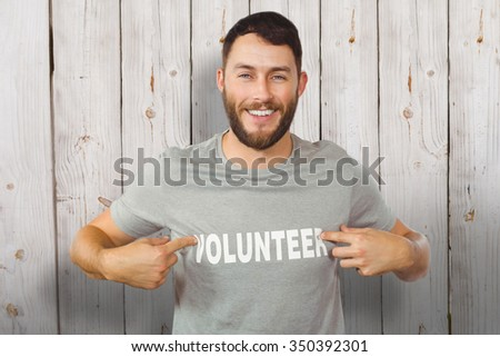 Man showing volunteer text on tshirt against wooden background