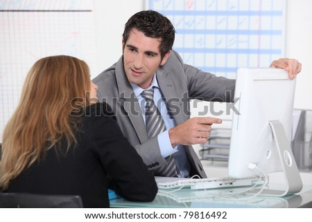 Man showing woman computer screen - stock photo