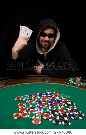 Man shows two aces and win hand in poker casino with chips on green felt - stock photo